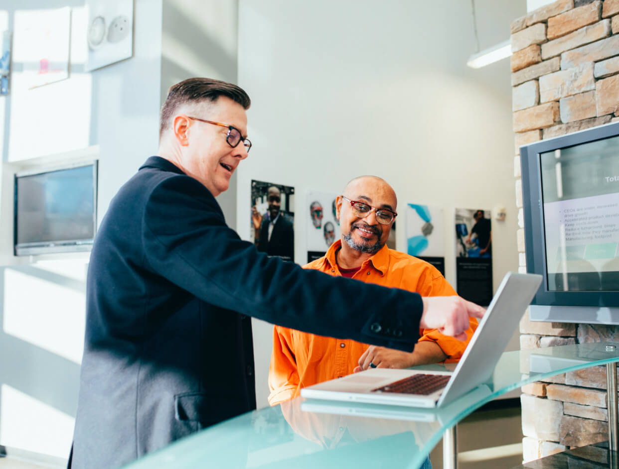 Professional man pointing at his computer screen while customer happily agrees.